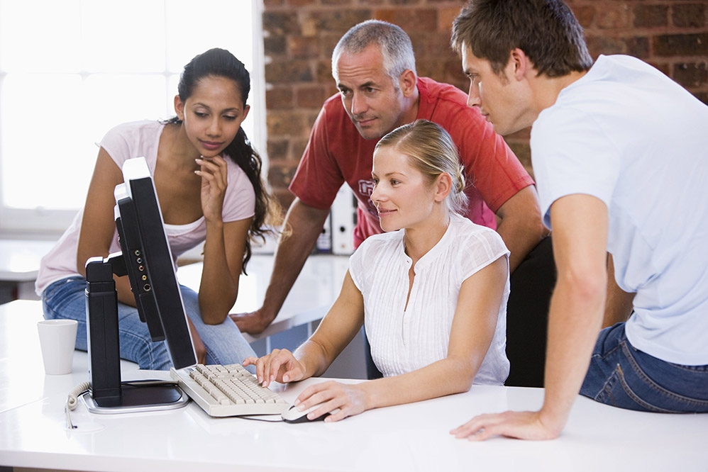 Group of employees looking at a computer