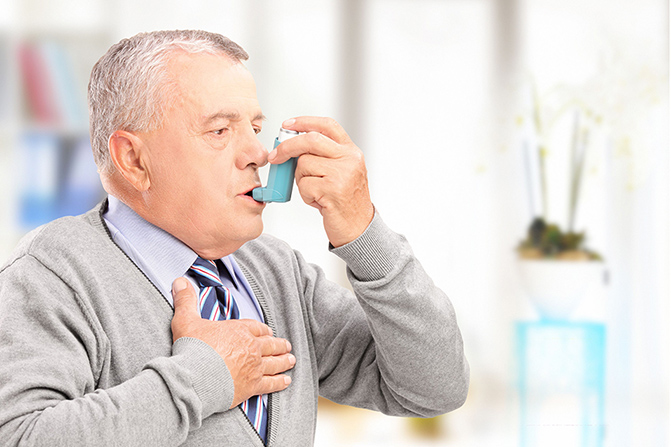 mature man treating asthma with inhaler at home